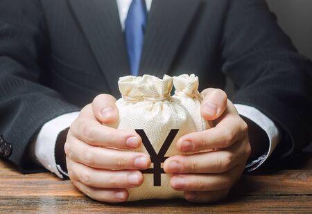 Businessman hugs yen yuan money bags. Granting financing business project or education. Provision financial loan credit. Bank deposit. Budget management, tax collection. Trade, economics. Corruption