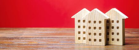Miniature wooden houses on a red background. Real estate concept. City. Agglomeration and urbanization. Market Analytics. Demand for housing. Rising and falling home prices. Population. Copy space 版權商用圖片
