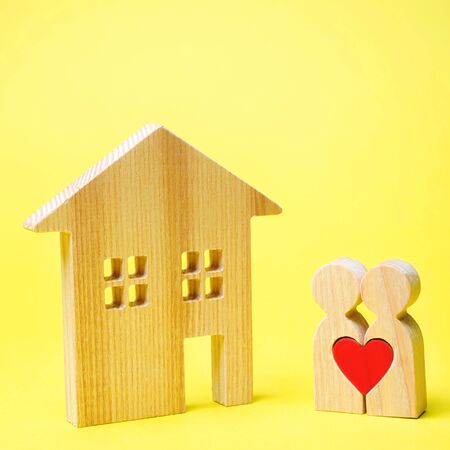 A couple of lovers is standing near the wooden house. Valentines Day. Affordable housing for young families. Rental Property. Mortgage and loan. The concept of finding an apartment or home 版權商用圖片