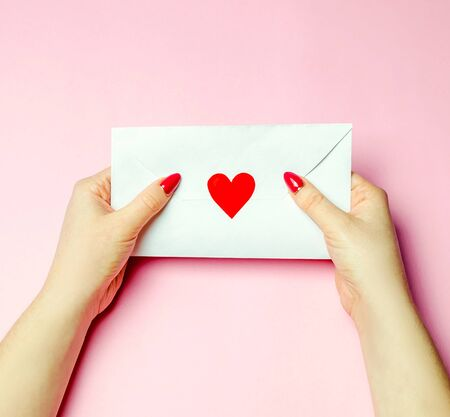 Female holding an envelope with a red heart. Valentines day concept. A love letter to the beloved. Greeting valentine card. Declaration of love. View from above. Flat lay