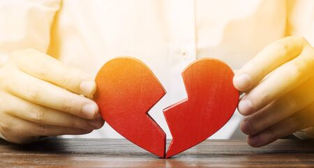 A man collects a red broken heart. Valentines Day concept. Love and relationships. Family psychotherapist services. Reconciliation. Saving the family. Search for the second half.