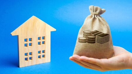 Money bag and wooden house. Real estate investment concept. Business and finance. Mortgage, loan, taxes, debts. Family home budget. Building, maintenance
