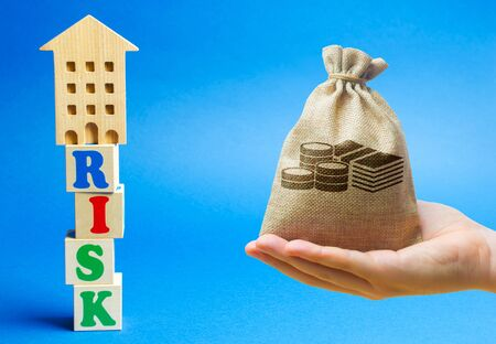 Wooden blocks with the word Risk and a miniature house with money bag. Real estate investment risks. Risky investments. Loss of property for non-payment. Debts. Mortgage tax.