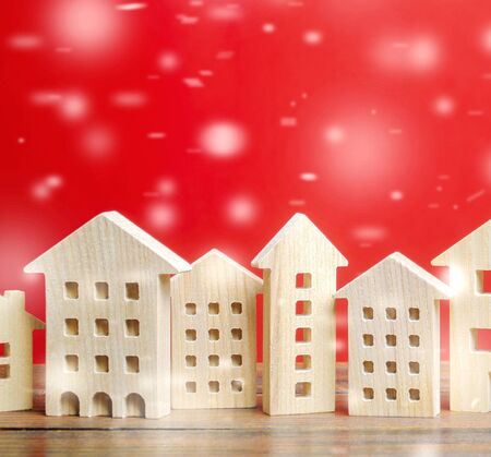 Miniature wooden houses and snowflakes on a red background. Christmas discounts and real estate sales. New Year or Xmas winter holiday. Decoration, celebration. Snow, snowfall. Housing, home
