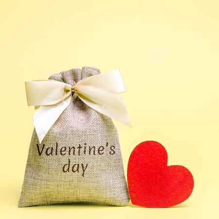 Bag with money and red heart with the word Valentines Day. Buying gifts to your loved one. Preparation for the holiday. Saving money and accumulation.