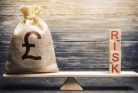 Money bag and wooden blocks with the word Risk on the scales. Business risk management and assessment. Strategic, financial and operational risks. Insurance. Economics and finance. Brexit Stock Photo