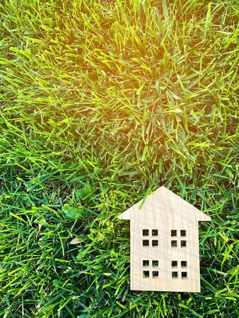 Miniature wooden house on green grass. Real estate concept. Modern housing. Eco-friendly and energy efficient house. Buying a home outside the city. Nature. Fresh air. Mortgage, loan. Place for text.