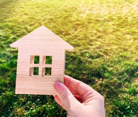 Miniature wooden house on green grass in female hands. Real estate concept. Modern housing. Eco-friendly and energy efficient house. Buying a home outside the city. Nature. Fresh air. Mortgage, loan.