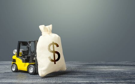 Yellow forklift carries a dollar money bag. Tax payment. Payment of taxes. Big contract, profitable deposit, take a loan. Wealth, investments in economy. financial aid. Inflation, price increases 版權商用圖片