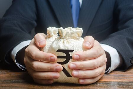Businessman hugs indian rupee money bags. Granting financing business project or education. Trade, economics. Corruption. Provision financial loan credit. Bank deposit. Budget, tax collection.