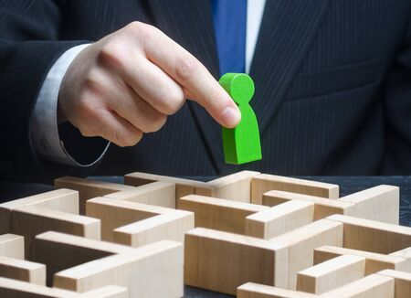 A male businessman holds a green figure over a maze. Make a path to success, provide support. Pass test, complete task. Professional skills development. Find a way out of the situation. Reach the goal 版權商用圖片