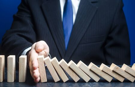 Businessman stops domino falling. Strategy development. Debt restructuring. Risk management concept. Reliable leader. Stop the destructive processes. Successful strong business and problem solving.