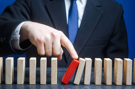 Businessman starts the process of falling dominoes. Starting work after stopping. Continuation of working, obstacle avoidance. maintainability. Correction of errors and malfunctions 版權商用圖片