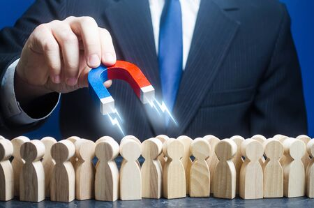 Man with a magnet is in search of candidates for work among the crowd. Recruiting talented workers, headhunters, human resources. Best choice. Search professionals specialists for open vacancies.