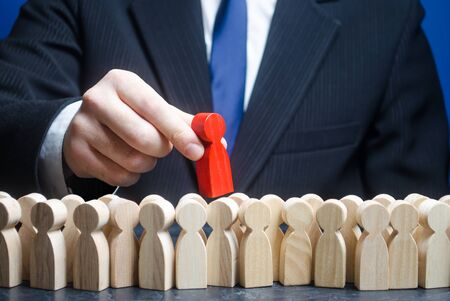 Businessman takes a red man out of a crowd of people. Finding the right person. Recruiting talented workers, headhunter, HR. Best choice. Search professionals specialists for open vacancies. 版權商用圖片