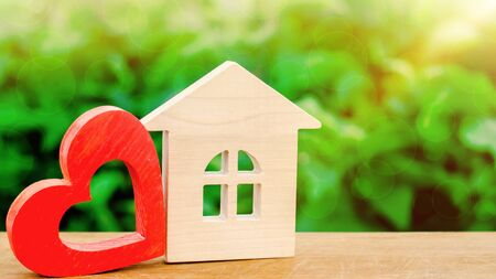 Wooden house and red heart. Concept of sweet home. Property insurance. A new home for family. Rent a house on Valentines Day. Family comfort. Affordable mortgage housing for young couples.