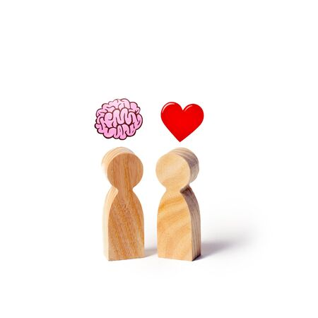 Two wooden figures with the image of the brain and heart. The balance between love and mind. Family versus career or work. Family psychology. Problem of choice.