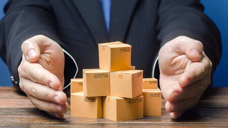 Businessman covers boxes goods. Business management. Commodity circulation import export. Support manufacturer, attracting investments, promoting products to new markets. Marketing sales, distribution