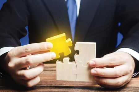 Businessman connects a golden part to puzzle assembly. Creating new product, Innovation development. Stakeholder management. Project completion. Find a solution. Right choice. Achieving Success