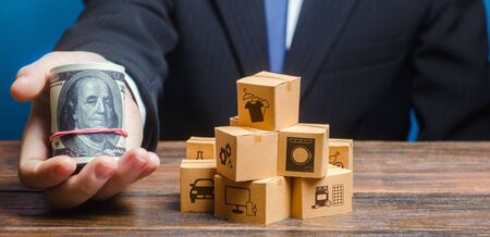 Businessman holds out a bundle of dollars near a pile of boxes. Profit, Superprofits. Investments financing in production, taxes, income revenues. Trade and exchange goods, offers for cooperation.