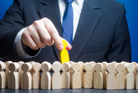 A businessman takes out best candidate from human crowd. A talented and skillful specialist, a born leader and professional. Hiring recruiting candidature. Meets high criteria requirements. Stock Photo