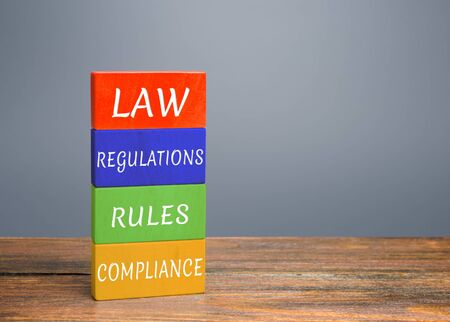 Colored blocks with words law, regulations, rules, compliance. Ease doing business. Quality criteria for goods, services. Protection national domestic producers manufacturers from strong competition Foto de archivo