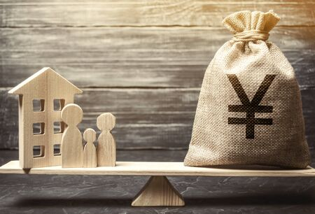 Money bag with yen / yuan and wooden house on scales with family. Fair value of real estate and housing. Payment of the mortgage interest rates. Redemption of taxes. Tax refund. Apartment valuation Stock Photo