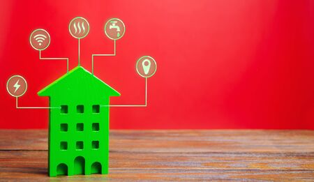 Miniature wooden house and symbols of public utilities. Choosing a house to buy, assessing the cost and condition of the building, location in the city. Repair and renovation, maintenance services Stock Photo