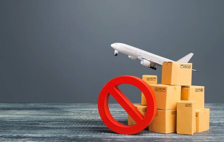 Cardboard boxes near a prohibition symbol NO and freight plane. Restrictions ban on import goods. Sanctions, trade embargo. Isolation quarantine. Manufacturers production slowdown. Flight cancellation