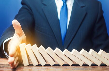 Businessman stops domino falling with his palm. Strategy development. Debt restructuring. Risk management concept. Successful strong business and problem solving. Stop the destructive processes.