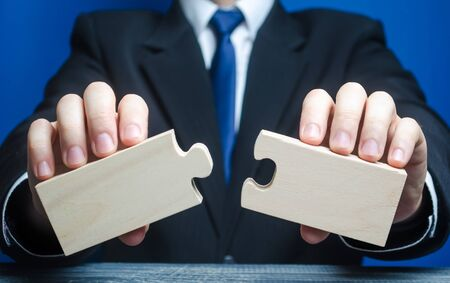 Businessman holds in hands two empty pieces of the puzzle. The process of connection into a single whole, assembly, creation of new. Business management, planning strategy. Two things for success.