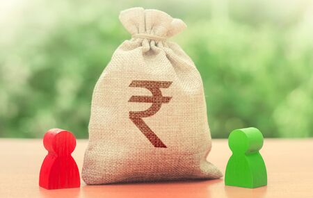 Indian rupee money bag and a deal between two persons. Business lending, leasing. Tender competitiona contract. Trade agreement. Negotiation process dealings. Dispute solution. Finance surety promise