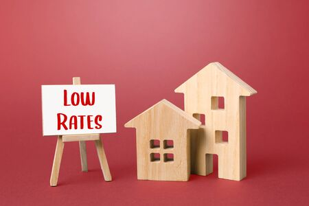 Figurines of houses and an low rates easel. Big promotions and discounts on home sales. Low demand for real estate and housing, economic downturn and recession. . Special purchase offers