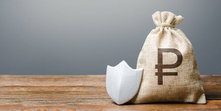 Russian ruble money bag and protection shield. Ease doing business. Protection of foreign investment in economy. Attractive lending conditions, rule of law, secure capital. Resistance economic shock Stock Photo