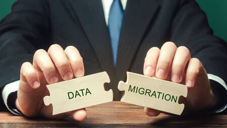 Businessman collects wooden puzzles with the words Data migration. Process of preparing, selecting, extracting data and transferring from one computer storage system to another.
