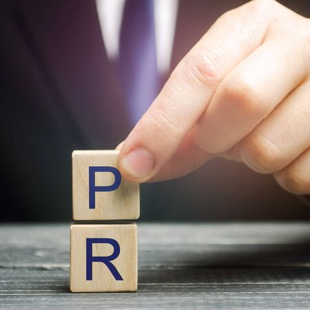 Businessman collects wooden blocks with the words PR -Public Relations. Management of information flows between the organization and the public. Social interaction. Strategic communication process. Banco de Imagens