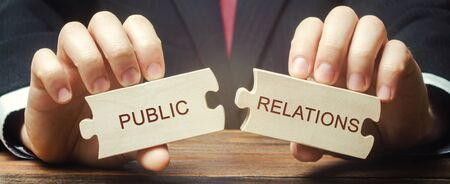 Businessman collects wooden puzzles with the words Public Relations. Management of information flows between the organization and the public. Social interaction. Strategic communication process. Foto de archivo