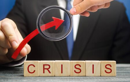 Businessman holds up arrow over blocks with the word Crisis. Increase instability of business and economy. Recession, stagnation, bankruptcy. Midlife crisis. Impoverishment. Debt and risk growth