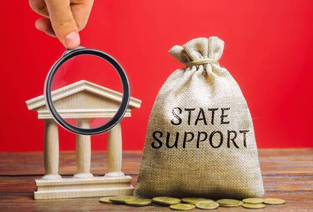 Money bag with the word State support and the bank building. Tax relief. Protection of manufacturers in the domestic market and promotion in foreign markets. Exemption from taxes. Small Business