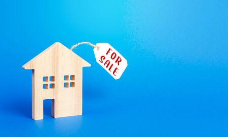 House figure and for sale price tag. Selling real estate, lower prices because of a falling market and reduced demand. Realtor Services. Investing in housing to save during an economic downturn. Stock Photo