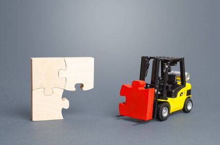 A forklift truck picks up the missing puzzle piece. Organization and systematization, step by step instructions. Procedure, key condition. Business planning. Contract road map. Priority task items Imagens