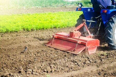 Tractor with milling machine loosens, grinds and mixes soil. Loosening the surface, cultivating the land for further planting. Farming and agriculture. Cultivation technology equipment