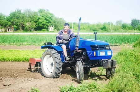 A farmer drives a tractor on a farm field. Agricultural cultivation technology equipment and technical transport. Loosening the surface, cultivating land for further planting. Farmer support subsidies