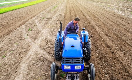 A farmer on a tractor cultivates a farm field. Soil milling, crumbling and mixing. Loosening surface, cultivating land for further planting. Agroindustry, farming. Preparatory work for a new planting. Imagens