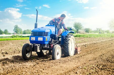 Farmer on a tractor with milling machine loosens, grinds and mixes soil. Loosening the surface, cultivating the land for further planting. Farming and agriculture. Cultivation technology equipment Banque d'images