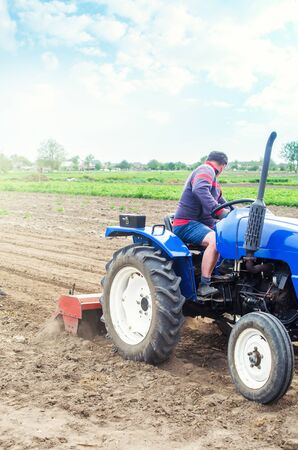 A farmer on a tractor cultivates a farm field. Soil milling, crumbling and mixing. Loosening the surface, cultivating the land for further planting. Agriculture, growing organic food vegetables.