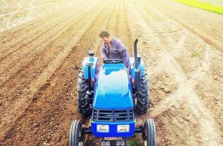 A farmer on a tractor cultivates a farm field. Soil milling, crumbling and mixing. Preparatory work for a new planting. Loosening surface, cultivating land for further planting. Agroindustry, farming. 스톡 콘텐츠