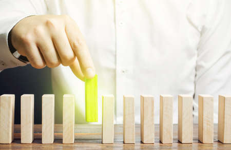 A man puts green dominoes in a row. Business management and processes. Correct errors, make improvements. Risk management, integration into upgrades to the system, implementation into legislation.