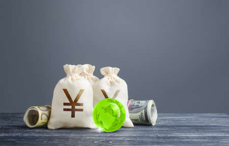 Yen yuan money bags. Banking financial system, world reserve currency. Economics, lending business. Dividends payouts. Investing in economy, replenishing budget with taxes. Trading, currency exchange
