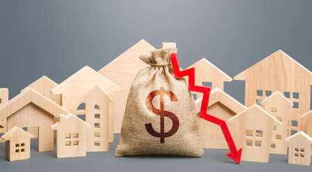City residential buildings and dollar money bag with a red down arrow. Low cost of real estate. Lower mortgage interest rates. Falling prices for rental apartments. Reducing demand for home buying Zdjęcie Seryjne